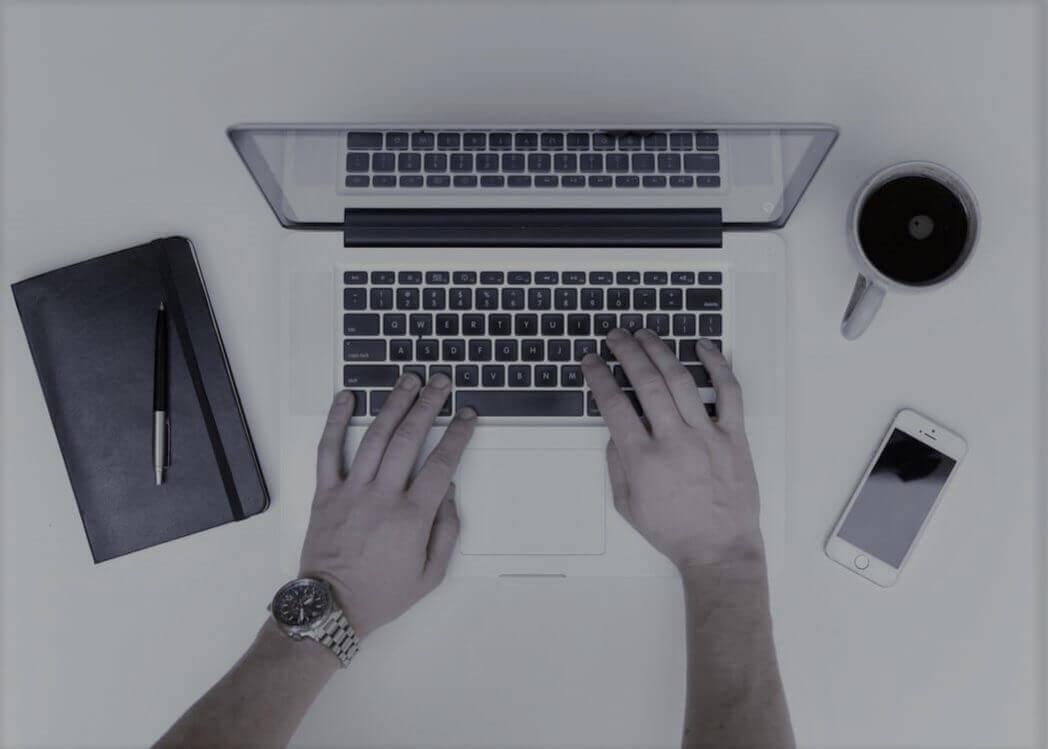 macbook med kaffekopp, anteckningsblock och iphone bredvid