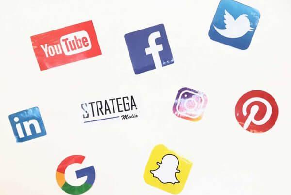 Vägg med bilder på sociala medier-ikoner samt Stratega Media's logotyp