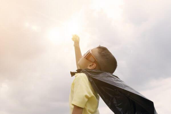 Barn med mantel och solglasögon som håller armen i luften